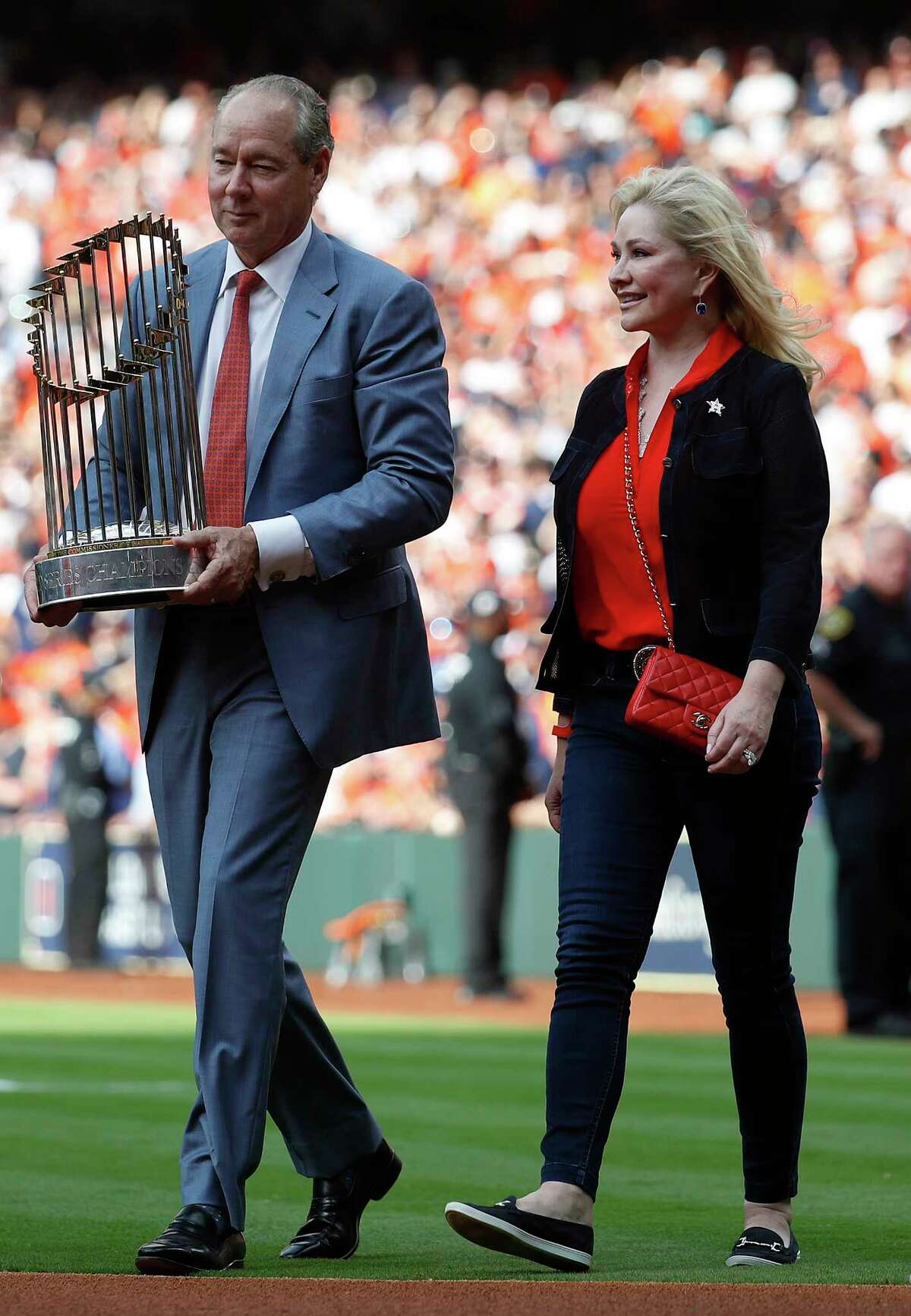 Houston Astros owner Jim Crane and hius wife walk out to the field with the World Series trophy during the pre-game ceremony before the start of the home opener during an MLB baseball game at Minute Maid Park, Monday, April 2, 2018, in Houston.