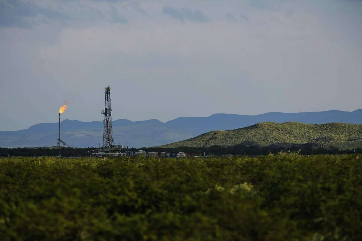 An Apache Corporation flare and drilling rig sit north of the Davis Mountains Friday, Sept. 16, 2016 in Balmorhea. The company recently announced the discovery of an estimated 15 billion barrels of oil and gas in the area and plans to drill and use hydraulic fracturing on the 350,000 acres surrounding the town. Apache has leased the mineral rights under the town and nearby state park, but has promised not to drill on or under either. While some residents worry that the drilling could affect the spring at the state park and impact tourism, others are excited for the potential economic boom the oil discovery and drilling could bring. ( Michael Ciaglo / Houston Chronicle )
