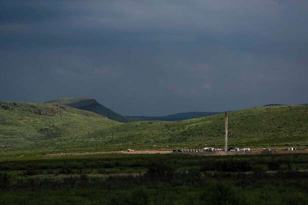 A drilling rig sits north of the Davis Mountains Friday, Sept. 16, 2016 in Balmorhea. Houston-based Apache Corporation recently announced the discovery of an estimated 15 billion barrels of oil and gas in the area and plans to drill and use hydraulic fracturing on the 350,000 acres surrounding the town. Apache has leased the mineral rights under the town and nearby state park, but has promised not to drill on or under either. While some residents worry that the drilling could affect the spring at the state park and impact tourism, others are excited for the potential economic boom the oil discovery and drilling could bring. ( Michael Ciaglo / Houston Chronicle )