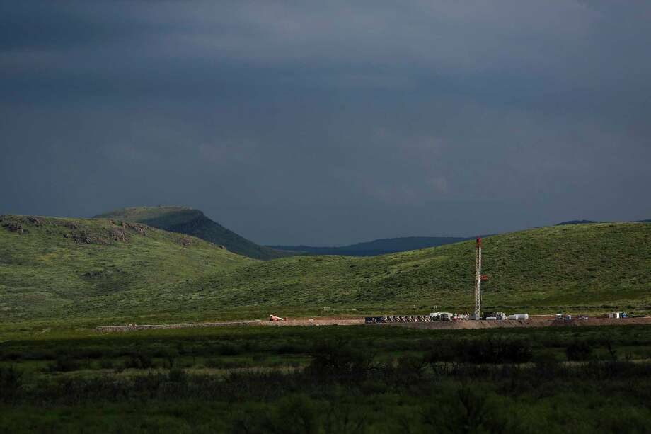 A drilling rig sits north of the Davis Mountains Friday, Sept. 16, 2016 in Balmorhea. Houston-based Apache Corporation recently announced the discovery of an estimated 15 billion barrels of oil and gas in the area and plans to drill and use hydraulic fracturing on the 350,000 acres surrounding the town. Apache has leased the mineral rights under the town and nearby state park, but has promised not to drill on or under either. While some residents worry that the drilling could affect the spring at the state park and impact tourism, others are excited for the potential economic boom the oil discovery and drilling could bring. ( Michael Ciaglo / Houston Chronicle ) Photo: Michael Ciaglo, Staff / Houston Chronicle / © 2016  Houston Chronicle