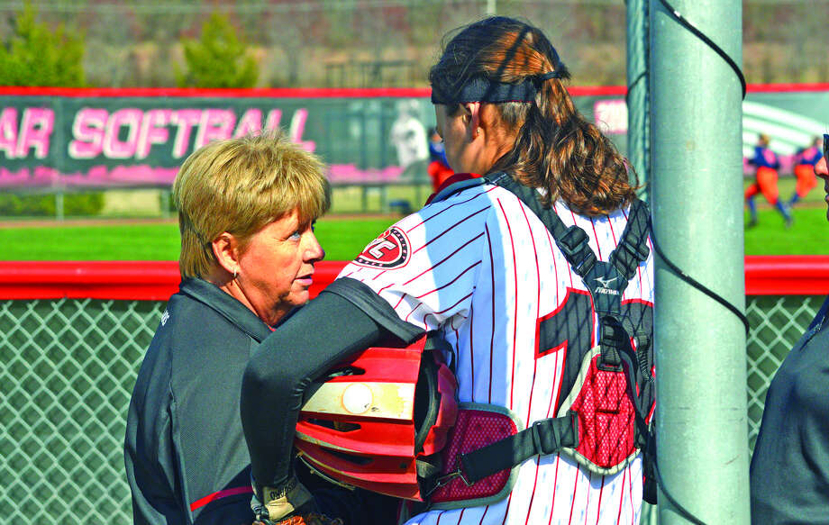 SIUE softball coach Sandy Montgomery, left, talks to Cougars catcher Sydney Bina before the March 21 home opener against Illinois.