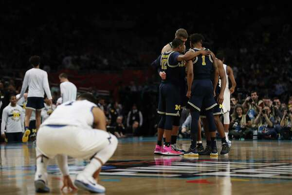 The Michigan Wolverines huddle prior to the start of the NCAA Championship game at the Alamodome. Kin Man Hui/San Antonio Express-News