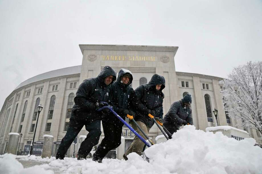 Men shovel snow from the sidewalks in front of Yankee Stadium before the New York Yankees home opener against the Tampa Bay Rays, Monday, April 2, 2018, in New York. (AP Photo/Seth Wenig) Photo: Seth Wenig / AP