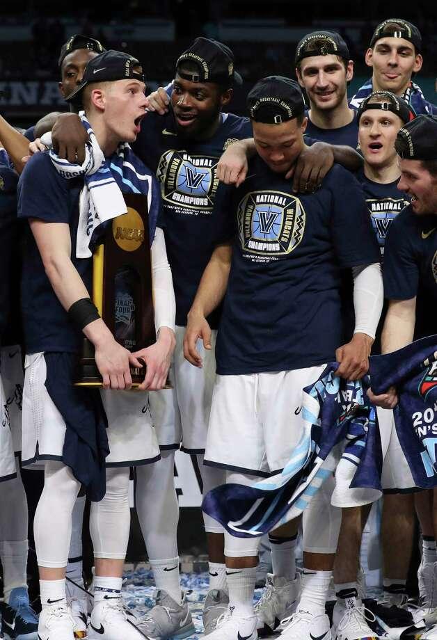 The Villanova Wildcats celebrate with the NCAA Championship trophy after defeating the Michigan Wolverines Monday night at the Alamodome.  Kin Man Hui/San Antonio Express-News Photo: Kin Man Hui, Kin Man Hui/San Antonio Express-News