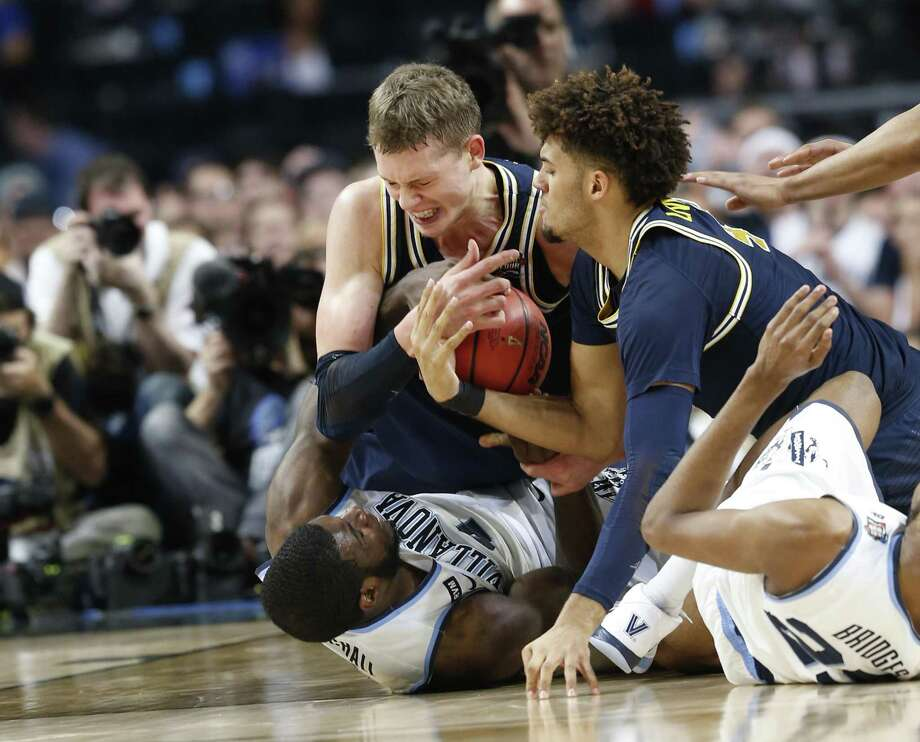 Villanova and Michigan players hit the floor for a loose ball in the first half of the Wildcats' 79-62 title game win. Photo: Edward A. Ornelas /San Antonio Express-News