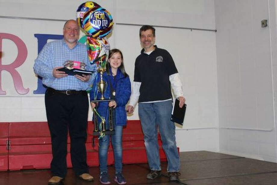 Middletown Macdonough Elementary School fifth-grade student Layla Pini, center, won the top prize in the fourth- to fifth-grade category of the SIFMA Foundation's annual InvestWrite Competition. At left is her father James Pini and, at right, STEM teacher John Ferrero. Photo: Contributed Photo