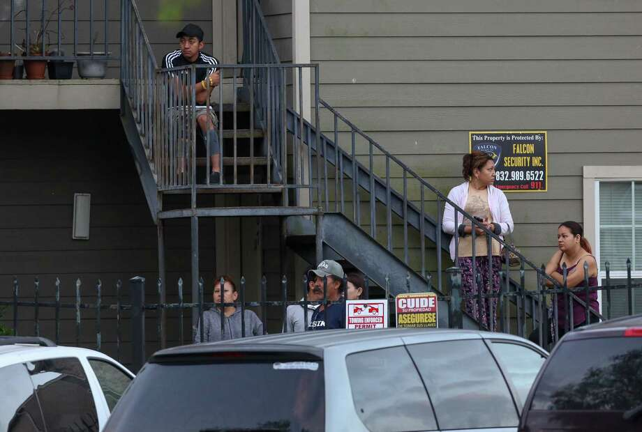 People inside the Bristol Court Apartments complex watch as Houston Police officers investigate the scene where a person was fatally shot on South Course Drive Tuesday, April 3, 2018, in Houston. Photo: Godofredo A. Vasquez, Houston Chronicle