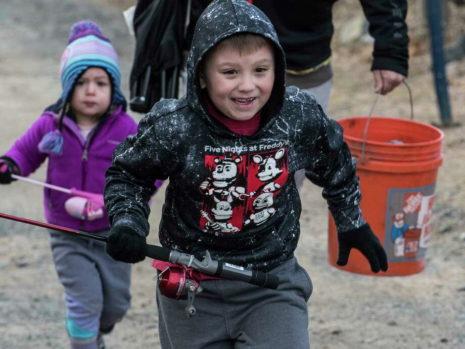 Garrett Paulsen, 6 and his little sister McKenna, 3, of Altamont run up the hill toward the Six Mile Waterworks to get a head start on the fishing activities as NYS DEC adds 1700 rainbow trout to the water of the reservoir  Tuesday April 3, 2018 in Albany, N.Y. (Skip Dickstein/Times Union) Photo: SKIP DICKSTEIN, Albany Times Union / 20043396A