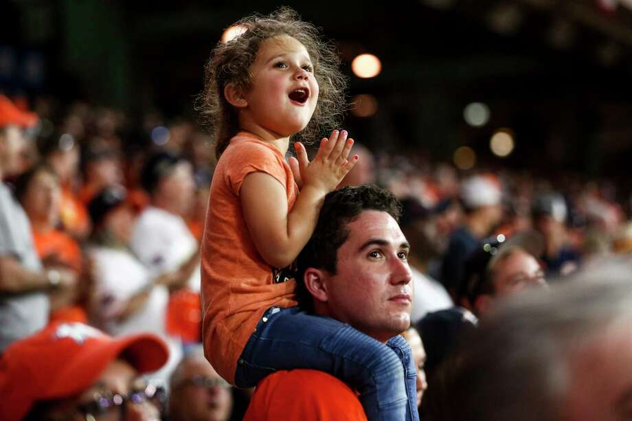 Sari Jones, 4, rides on the shoulders of her father, Mike Jones, during the seventh-inning stretch. Like many Astros fans, she says her favorite player is Jose Altuve. Photo: Michael Ciaglo / Michael Ciaglo