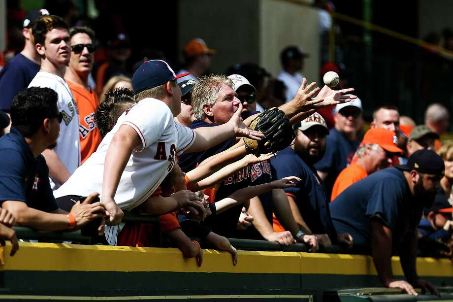 Fans reach through a sea of hands for a ball tossed up into the Crawford Boxes during batting practice. Photo: Michael Ciaglo / Michael Ciaglo