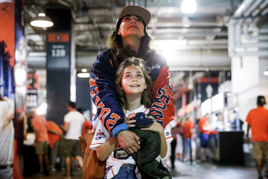 "Laurel Ross wraps her arms around her daughter, Tinsley, 9, as they watch the game on one of the televisions on the concourse in an attempt to escape an annoying brother in the stands. ""I've been bringing them here for so long that they are actually getting into the games,"" Ross said of her kids. ""They used to just play in the playground, but baseball is in our blood."" Photo: Michael Ciaglo / Michael Ciaglo"