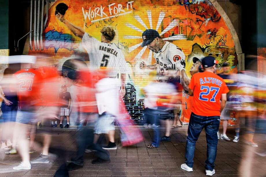 Fans walk past the Astros Street Art display in Home Run Alley as they head to their seats before the Houston Astros home opener against the Baltimore Orioles at Minute Maid Park Monday, April 2, 2018 in Houston. The graffiti artwork was painted by local artist Franky Cardona.