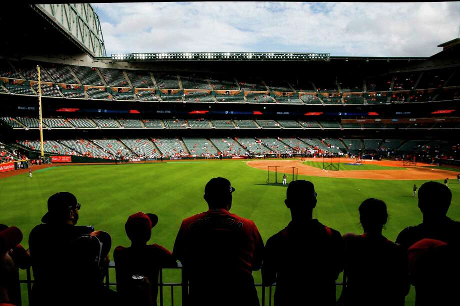 Leaning on the railing in left-center field, fans watch batting practice before the Astros' home opener. Photo: Michael Ciaglo / Michael Ciaglo