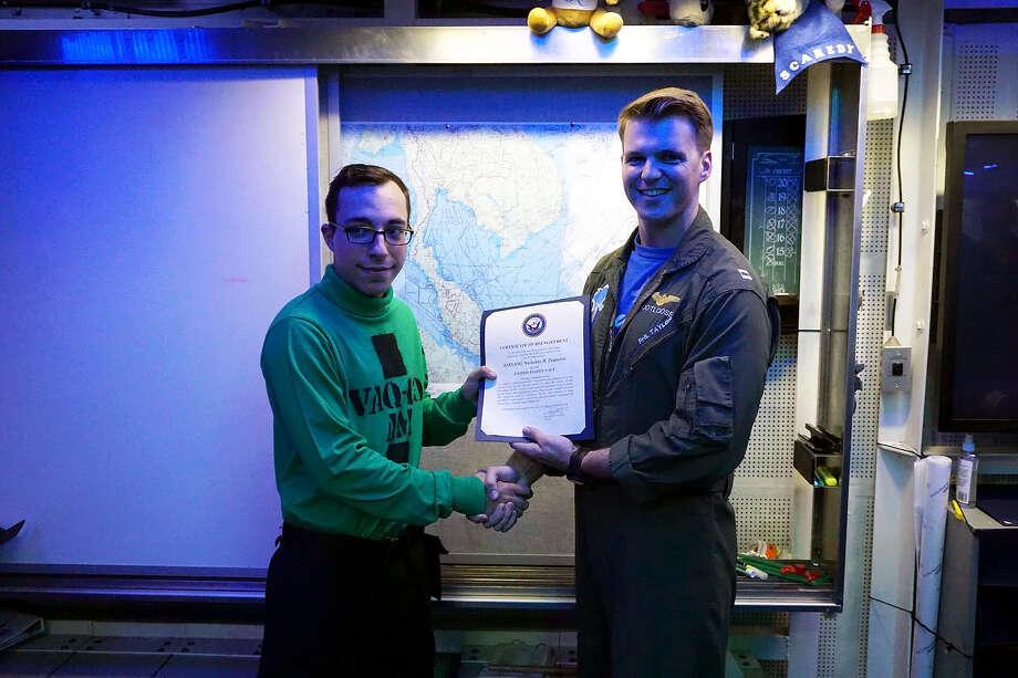 Petty Officer 2nd Class Nicholas Zequeira (left) receives his re-enlistment certificate. Photo: Courtesy Photo