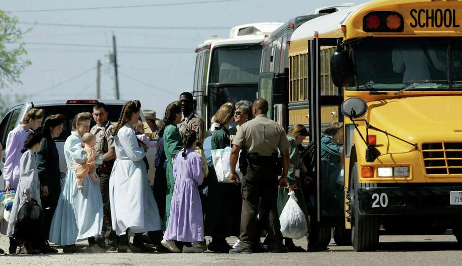 Law enforcement officials assist members of the Fundamentalist Church of Jesus Christ of Later Day Saints onto a school bus in Eldorado, Texas, Sunday, April 6, 2008. The group was relocated to San Angelo, Texas. Photo: Tony Gutierrez, STF / AP / AP