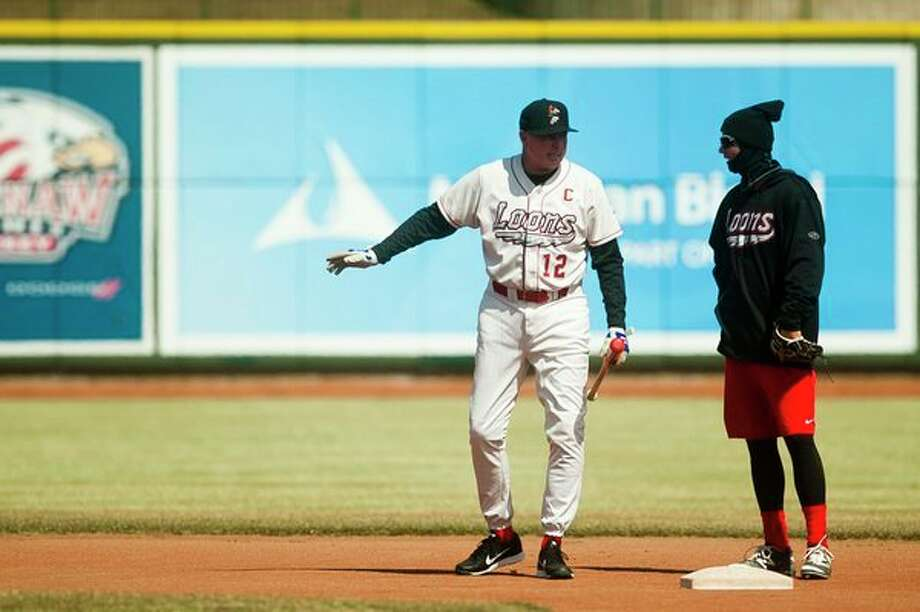 Great Lakes Loons Manager John Shoemaker chats with Loons third baseman Zach McKinstry during their first practice of the season on Monday at Dow Diamond. (Katy Kildee/kkildee@mdn.net)