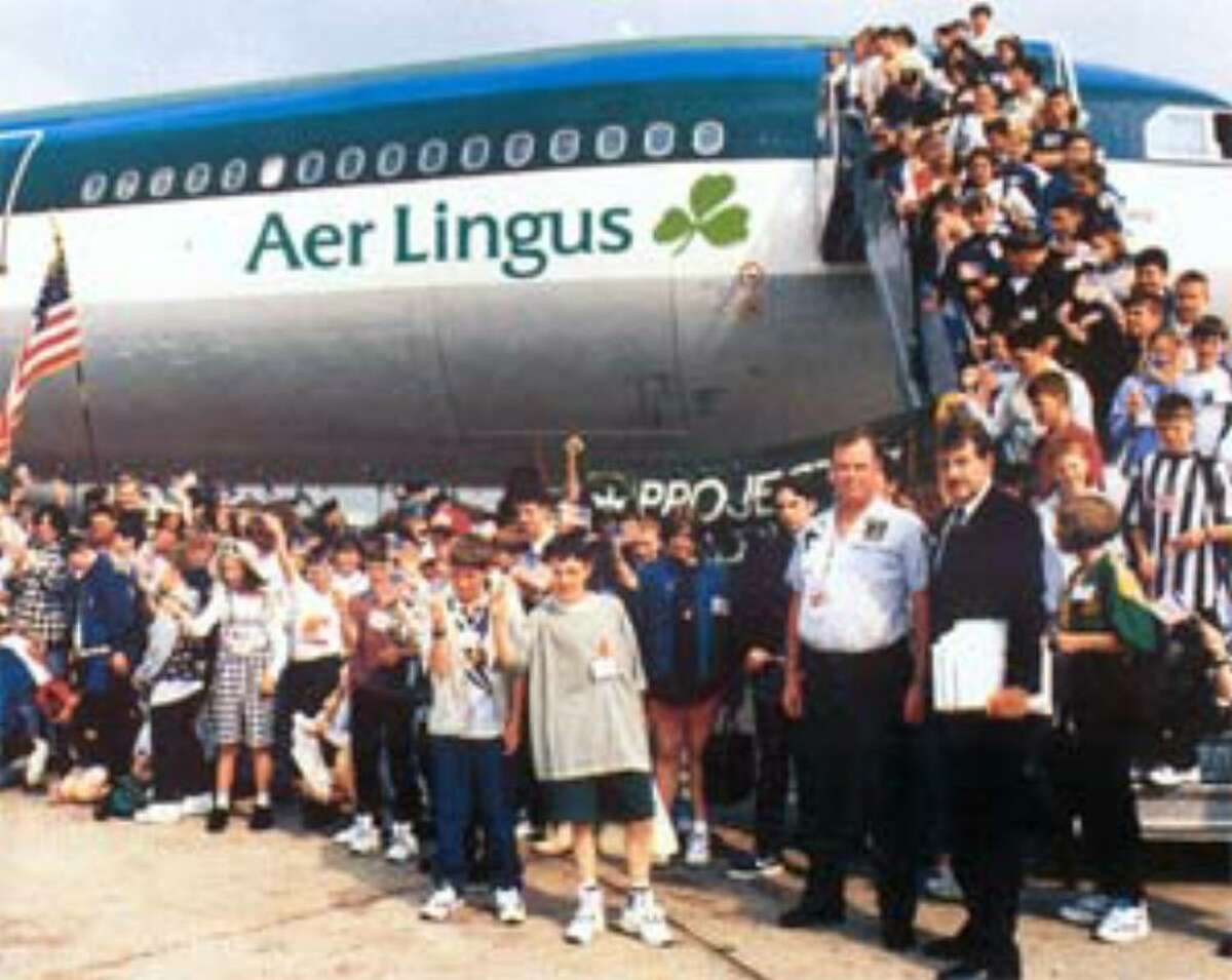 Denis Mulcahy, founder of Project Children, and James Ruoff of the U.S. Customs and Border Protection welcome children from Northern Ireland at Kennedy Airport in New York during an earlier summer visit. ( Project Children photo )