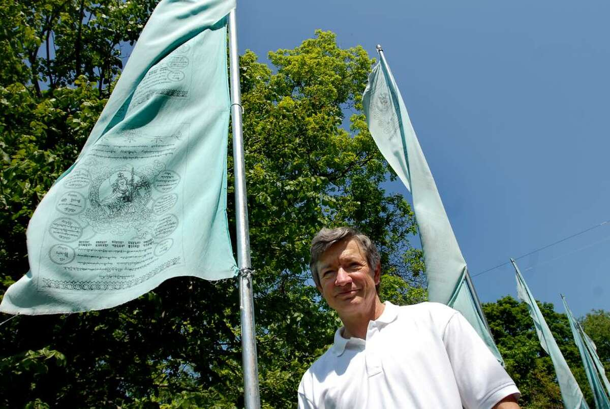 Executive director David Rand stands by a set of Tibetan prayer flags at the Tenzin Gyatso Institute in Berne. (Cindy Schultz / Times Union)