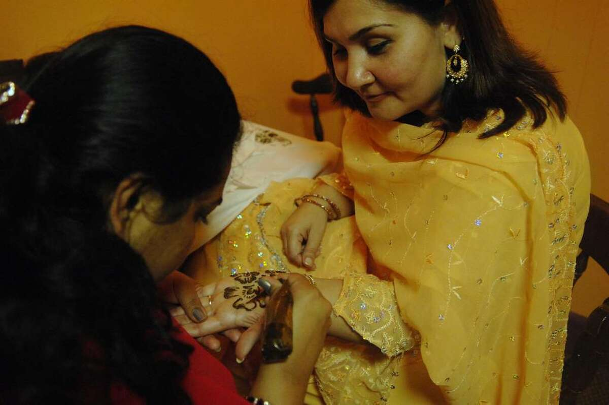 Humaira Khan, right, who with her husband owns Tandoori restaurant, has a henna tattoo applied to her hand by Kranthi Penta, left, owner of Kranu Beauty Parlor of Clifton Park at the Chaand Raat celebration at Tandoori restaurant in Colonie on Thursday evening, Nov. 26. The bazaar is held the eve before Eidul Adha, or feast of sacrifice, which is celebrated after hajj pilgrimage to Mecca. (Paul Buckowski / Times Union)
