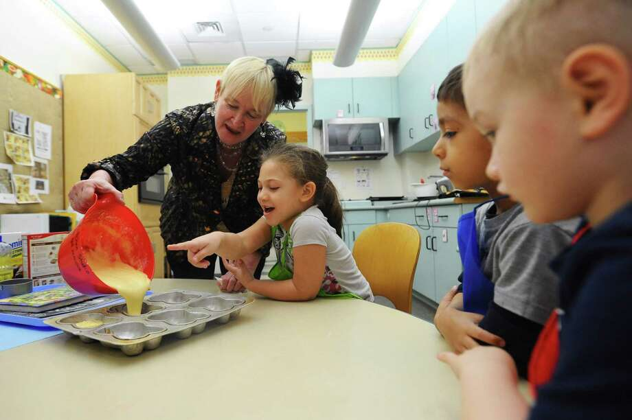 Instructional coordinator Debby Schreiner shows preschooler Emily, and five of her classmates, how to create and then pour batter while baking during a cooking studio class inside the Children's Learning Center in Stamford, Conn. on Tuesday, April 3, 2018. Photo: Michael Cummo / Hearst Connecticut Media / Stamford Advocate