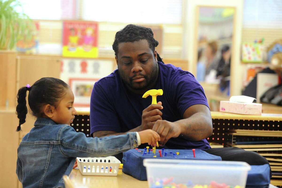 Teacher Akiem Ruffin plays with Giselle during preschool inside the Children's Learning Center in Stamford, Conn. on Tuesday, April 3, 2018.