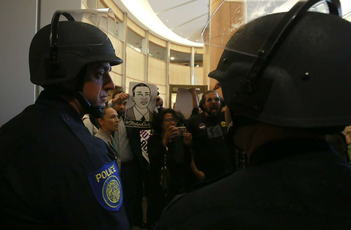 File -In this March 27, 2018, file photo, helmeted Sacramento police officers block the entrance to the Sacramento City Council chambers from demonstrators protesting the shooting death of Stephon Clark by Sacramento Police, in Sacramento, Calif. Sacramento Police Chief Daniel Hahn, the city's first black police chief, is an unlikely officer, growing up in a tough neighborhood of California's capital city and having his own early run-ins with police. He is struggling to find the right balance of reforms after the fatal shooting of Clark by his officers. (AP Photo/Rich Pedroncelli, File)