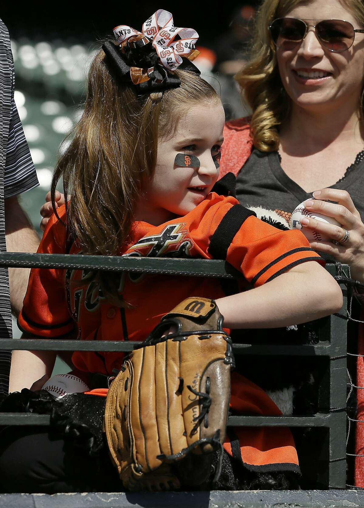 Emily Scadina, 6, of San Jose watches batting practice before the start of an opening day baseball game between the San Francisco Giants and the Seattle Mariners Tuesday, April 3, 2018, in San Francisco.
