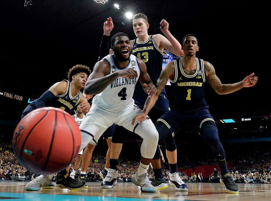 Villanova's Eric Paschall (4) reacts as he loses the control of the ball against Michigan's Moritz Wagner (13) and Charles Matthews (1) during the first half in the championship game of the Final Four NCAA college basketball tournament, Monday, April 2, 2018, in San Antonio. (AP Photo/Eric Gay) Photo: Eric Gay, STF / Copyright 2018 The Associated Press. All rights reserved.