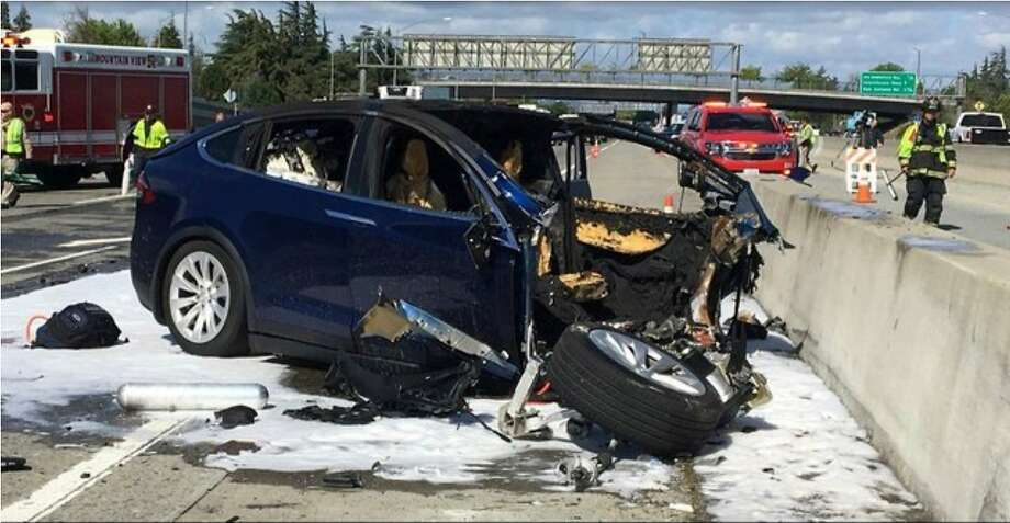 FILE - In this March 23, 2018 file photo provided by KTVU, emergency personnel work a the scene where a Tesla electric SUV crashed into a barrier on U.S. Highway 101 in Mountain View, Calif.  Tesla says, Saturday, March 31,  the vehicle in a fatal crash last week in California was operating on Autopilot, the latest accident to involve self-driving technology. The automaker says the driver, who was killed in the accident, did not have his hands on the steering wheel for six seconds before the crash. Tesla says its Autopilot feature, which can keep speed, change lanes and self-park, requires drivers to keep their eyes on the road and hands on the wheel to take control of the vehicle to avoid accidents. (KTVU via AP) Photo: Associated Press