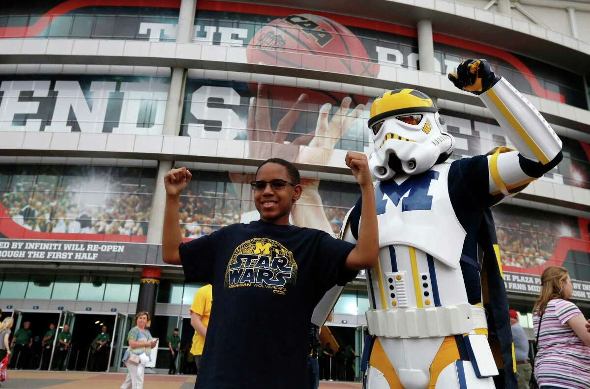 Michigan fans pose for a picture as they arrive at Alamodome before the championship game of the Final Four NCAA college basketball tournament between Michigan and Villanova, Monday, April 2, 2018, in San Antonio. (AP Photo/Brynn Anderson)