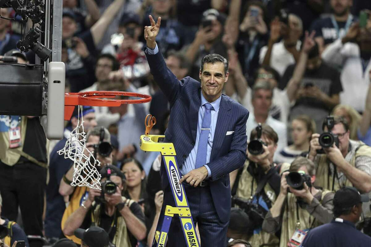 """Villanova head coach Jay Wright waves the Villanova """"V"""" to the fans after cutting the net after beating Michigan to win the NCAA National Championship at the Alamodome Monday, April 2, 2018 in San Antonio, Texas. Villanova are National Champions, beating Michigan 79-62. (Steven M. Falk/Philadelphia Inquirer/TNS)"""