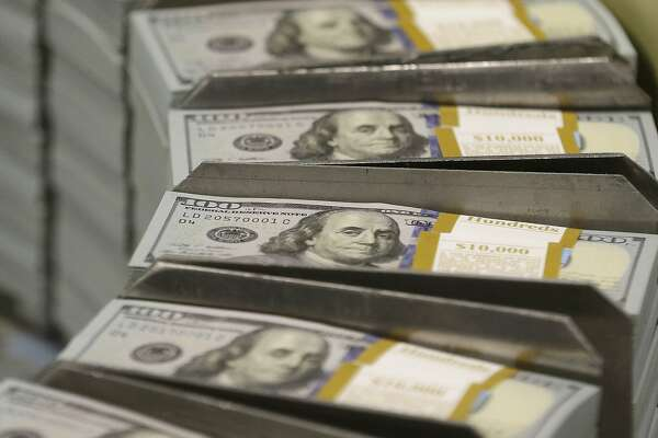 In this Sept. 24, 2013 file photo, cut stacks of $100 bills make their way down the line at the Bureau of Engraving and Printing Western Currency Facility in Fort Worth, Texas. According to a study released on Tuesday, April 3, 2018, middle-aged Americans who experienced a sudden, large economic blow were more likely to die during the following years than those who didn�t. The heightened danger of death after a devastating loss, which researchers called a �wealth shock,� crossed socio-economic lines, affecting people no matter how much money they had to start. (AP Photo/LM Otero)