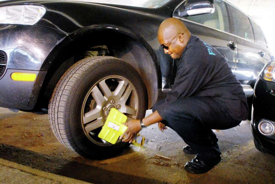A PayLock employee places a self-releasing boot on a car in Norwalk, which is believed to be the only state municipality using these devices. Photo: File Photo