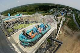 """FILE - In this July 9, 2014, file photo, riders go down the water slide called """"Verruckt"""" at Schlitterbahn Waterpark in Kansas City, Kan. Late Monday, April 2, 2018, federal authorities in Dallas arrested John Timothy Schooley, one of the designers of the water slide that decapitated a 10-year-old boy in 2016. Schooley and Jeffrey Henry, a co-owner of Texas-based Schlitterbahn Waterparks and Resorts, were indicted last week by a grand jury in Kansas. Schooley will be held in Dallas pending his arraignment and extradition to Kansas on charges that include second-degree murder. (AP Photo/Charlie Riedel, File)"""