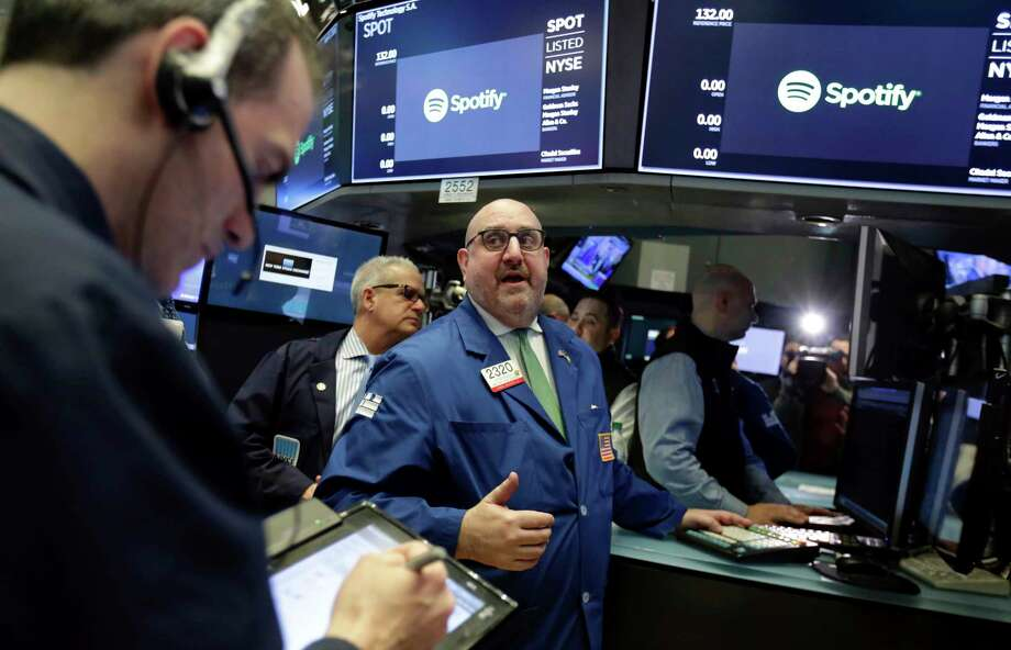 Specialist Peter Giacchi, center, stands on the floor of the New York Stock Exchange, Tuesday, April 3, 2018. Spotify Inc. will make its stock market debut Tuesday, casting a spotlight on its early lead in music streaming. (AP Photo/Richard Drew) Photo: Richard Drew / AP