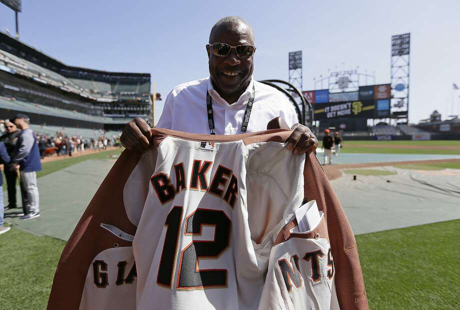 Former manager Dusty Baker shows off the lining of his sport coat before the start of an Opening Day baseball game between the San Francisco Giants and the Seattle Mariners. Baker recently rejoined his former team as a special advisor to San Francisco Giants CEO Larry Baer. Photo: Eric Risberg / Associated Press