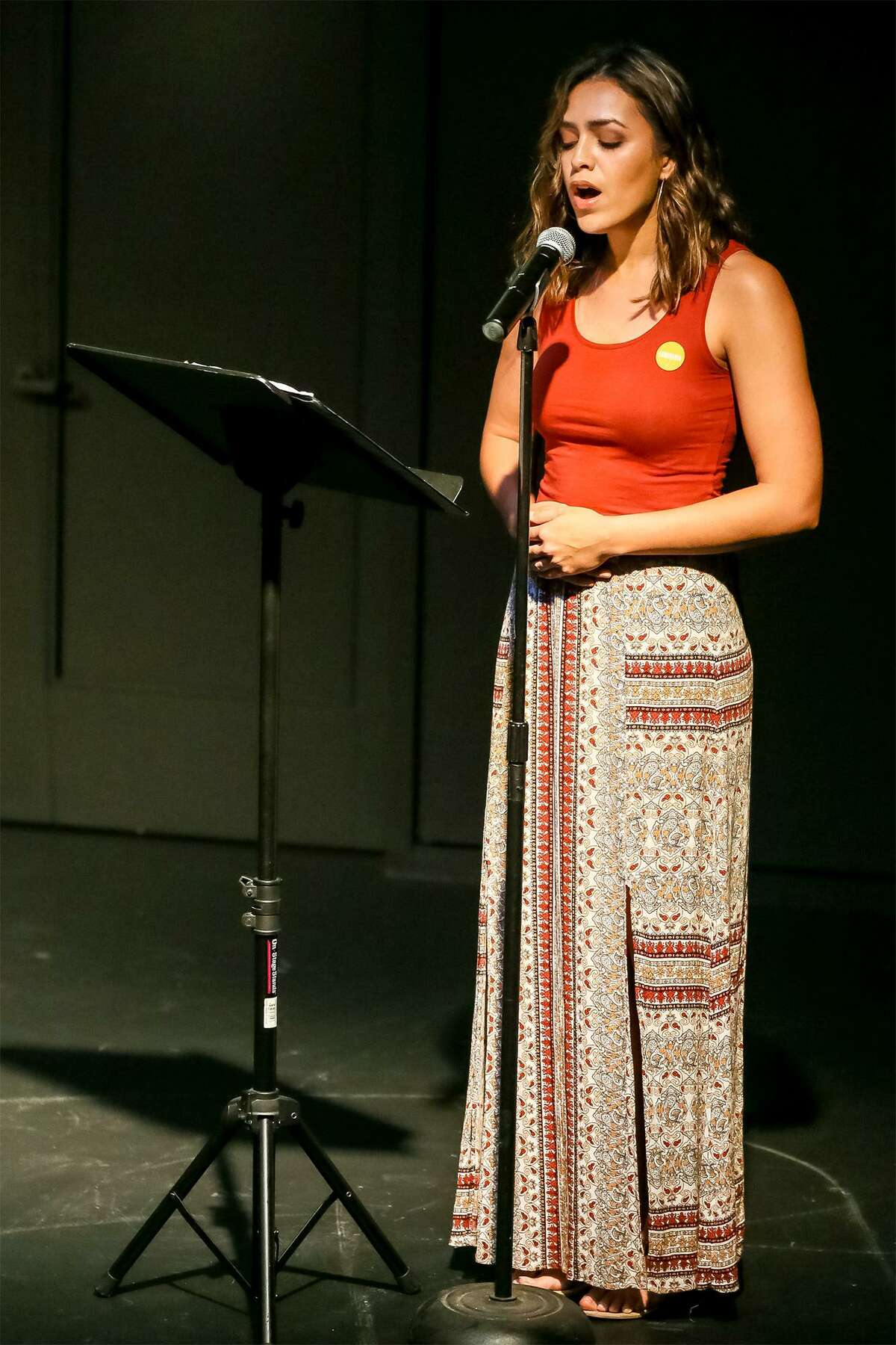 """Celeste Ramirez sings """"Lone Star,"""" a song written by music director and composer Nathan Felix, at Tuesday's Luminaria press conference."""