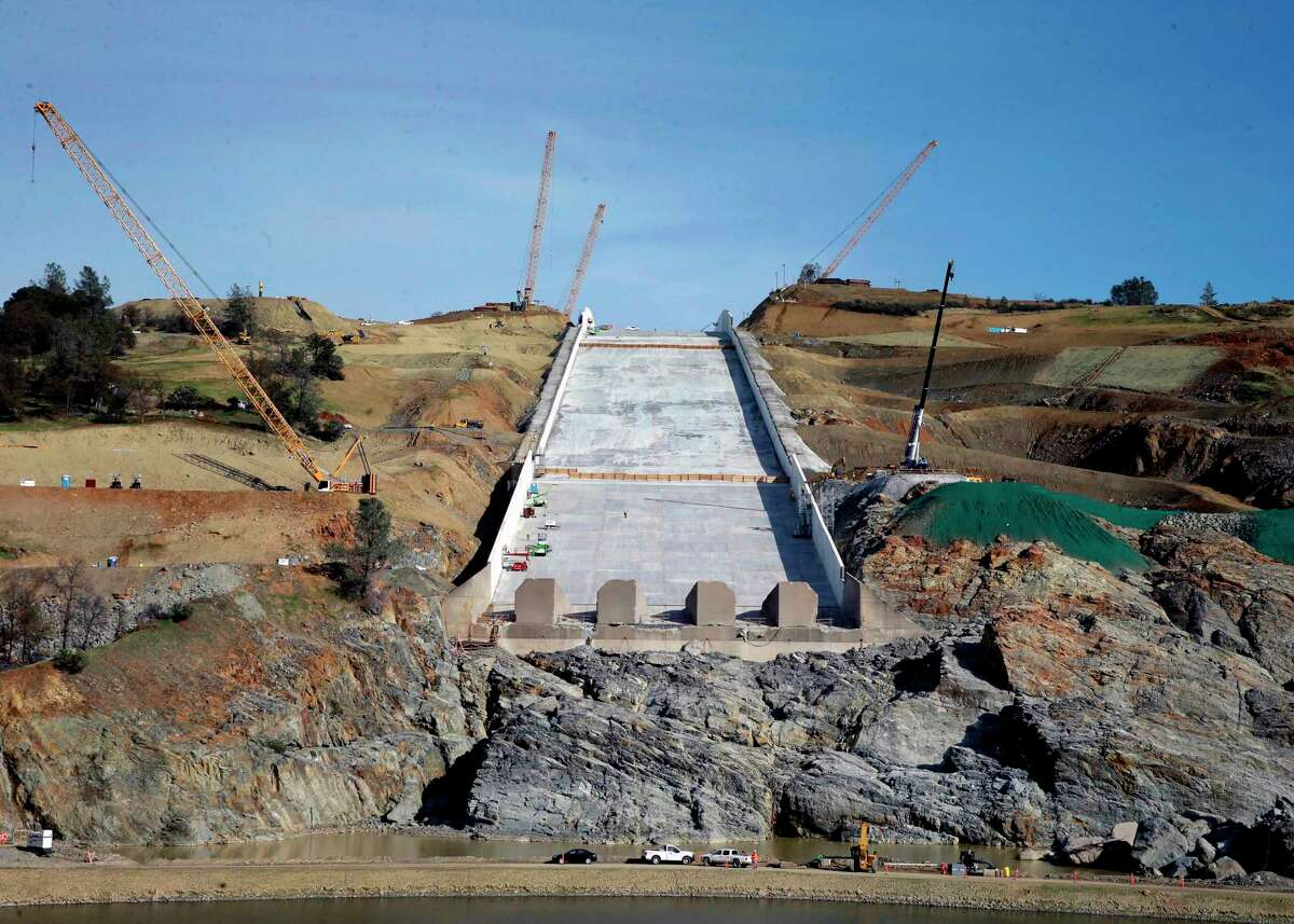 FILE--In this Nov. 30, 2017, file photo, work continues on the Oroville Dam spillway, in Oroville, Calif. California water officials say they may have to use the partially rebuilt spillway at Oroville Dam for the first time since they began repairs to the badly damaged structure last summer. Department of Water Resources officials said Tuesday, April 3, 2018, that anticipated storms could send trigger releases this week or next.