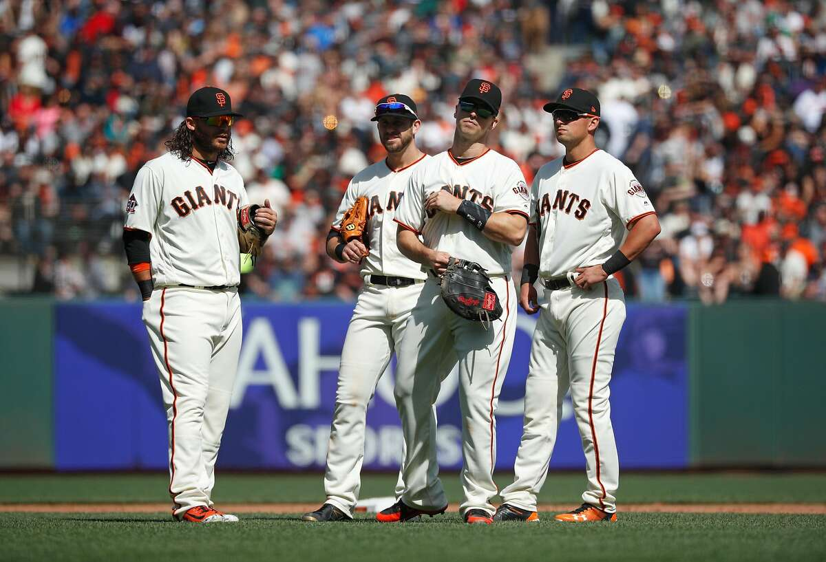 The Giants' infield ( lto r) Brandon Crawford, Evan Longoria, Buster Posey and Joe Panik during a picthing chang during the home opener for the San Francisco Giants as they prepare to take on the Seattle Mariners at AT&T Park in San Francisco, Calif., on Tues. April. 3, 2018.