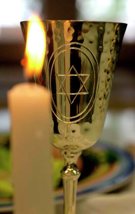 A candle burns in front of a wine cup — objects that are part of the annual Passover Seder. Passover is the Jewish holiday commemorating the liberation of the Israelites from Egyptian slavery. Photo: Johnny Hanson, Staff / Houston Chronicle / Houston Chronicle