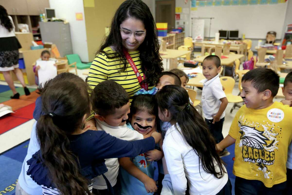 Pre-K teacher, receives a group hug from her students on the last day of school at John F. Kennedy Elementary School Wednesday, May 25, 2016, in Houston, Texas.