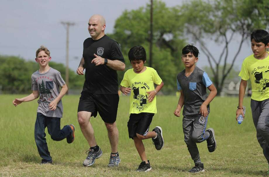 "Bexar County Sheriff Javier Salazar runs with Losoya Intermediate School students Daniel Wilkinson (from left), Adrian San Miguel, Luis Villa and David Moreno to fulfill a social media challenge put up by the students on Tuesday, Apr. 3, 2018. Salazar met up with fifth and sixth-graders from Losoya Intermediate's ""Kids Influencing Positive Change"" (KIPC) program who challenged the county's highest law enforcement officer to go on a run. About 150 students in the program joined the sheriff and ran laps on a practice field in the Southside Independent School District. The nonprofit Forward in Fitness matched Salazar with KIPC for the workout. (Kin Man Hui/San Antonio Express-News) Photo: Kin Man Hui, Staff / San Antonio Express-News / ©2018 San Antonio Express-News"