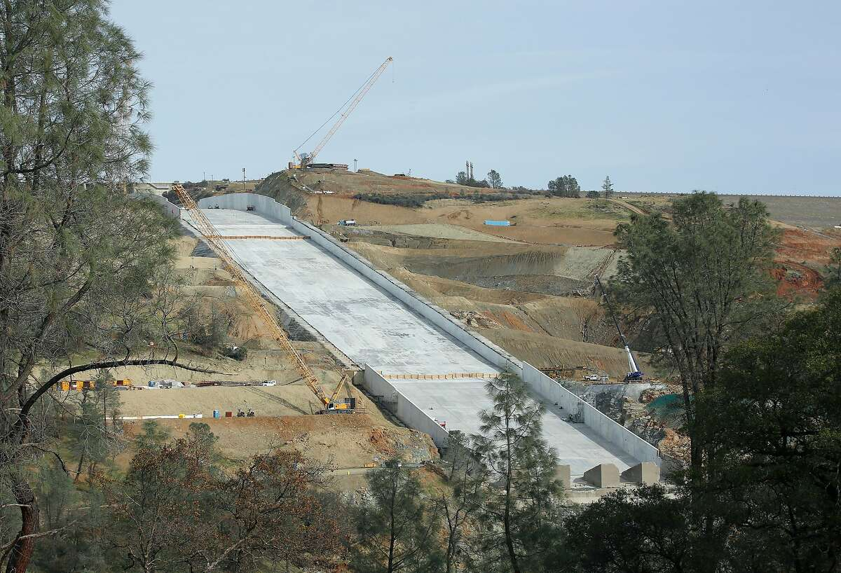 FILE--In this Nov. 30, 2017, file photo, work continues on the Oroville Dam spillway, in Oroville, Calif. California water officials say they may have to use the partially rebuilt spillway at Oroville Dam for the first time since they began repairs to the badly damaged structure last summer. Department of Water Resources officials said Tuesday, April 3, 2018, that anticipated storms could send trigger releases this week or next. (AP Photo/Rich Pedroncelli, file)