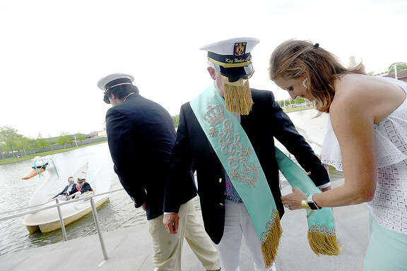 Neches King LXX Mark Smith has his royal garb affixed by Gillian Jenkins after arriving via swan paddle boats with his court for the Neches River Festival's unveiling ceremony at the Event Centre Tuesday.  Photo taken Tuesday, April 3, 2018 Kim Brent/The Enterprise