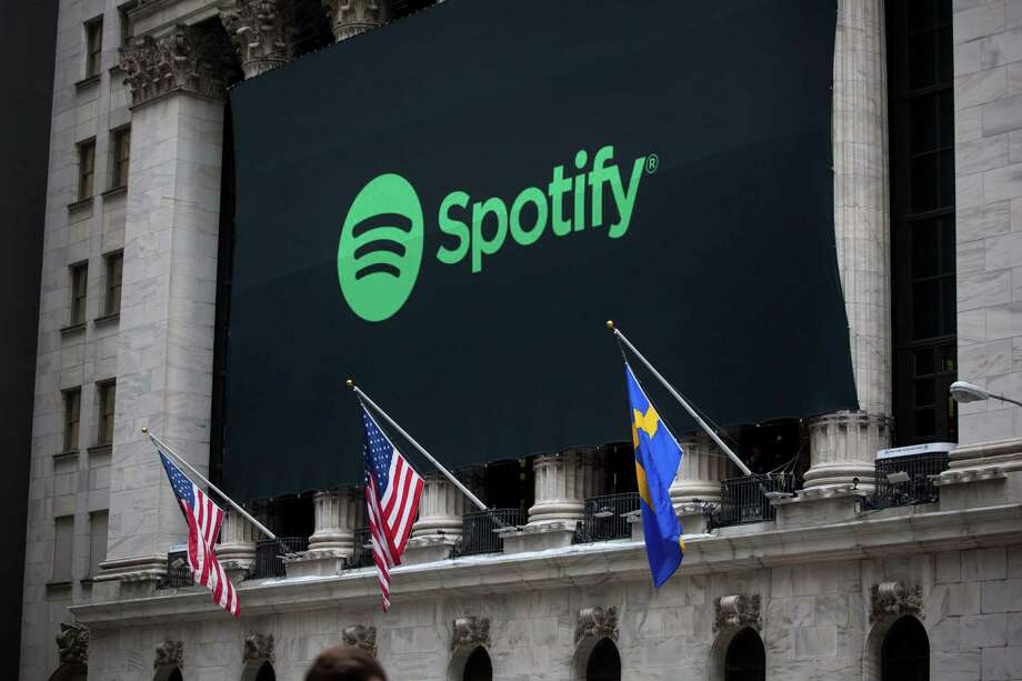 American and Swedish flags fly below Spotify Technology signage displayed outside New York Stock Exchange during the company's first day of trading in New York Tuesday. Photo: Michael Nagle / Bloomberg / © 2018 Bloomberg Finance LP