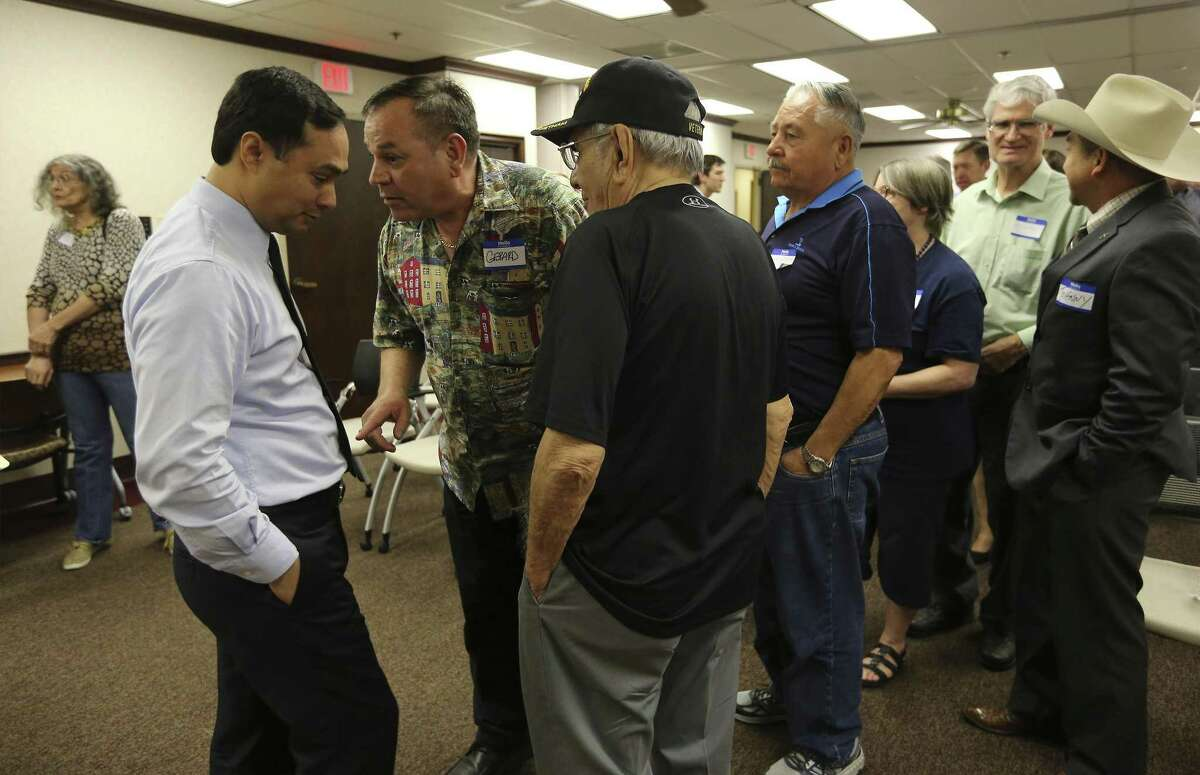 Gerard Villalobos and his father, Jesse, both military veterans, talk to Democratic U.S. Rep. Joaquin Castro after a town hall for constituents at his district office on Tuesday.
