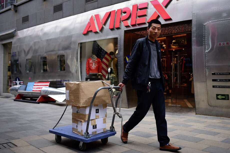 A man pulls a trolley with goods past a store in Beijing Tuesday. Photo: WANG ZHAO, Contributor / AFP/Getty Images / AFP or licensors