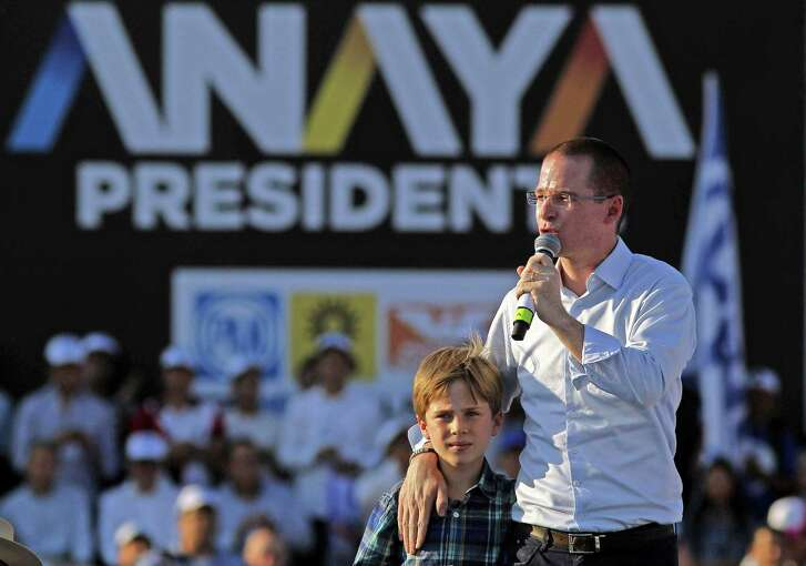 "Mexico's presidential candidate Ricardo Anaya, standing for the ""Mexico al Frente"" Coalition of the PAN-PRD parties, and his son Mateo, speaks to his supporters during his second campaign rally, in Celaya, Guanajuato State, Mexico on April 1, 2018.  The campaign for Mexico's July 1 presidential election officially opened on March 30. / AFP PHOTO / ULISES RUIZULISES RUIZ/AFP/Getty Images"