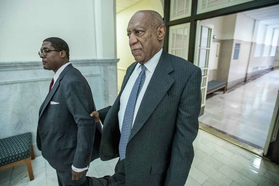 Bill Cosby, center, holds onto Andrew Wyatt, left, during a short break from Courtroom C at the Montgomery County Courthouse in Norristown, Pa., on the second day of jury selection in his sexual assault retrial Tuesday, April 3, 2018.  (Michael Bryant/The Philadelphia Inquirer via AP, Pool) Photo: Michael Bryant / Pool The Philadelphia Inquirer
