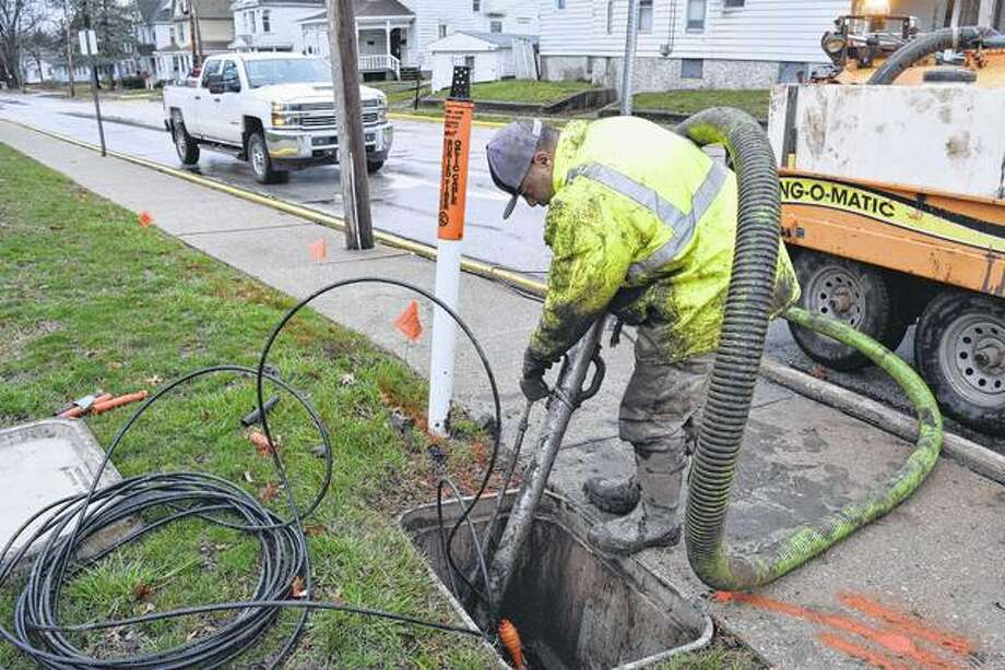 Tim Banks of Jacksonville, an employee of Chief Boring Service of Olney, uses a hydraulic vacuum Tuesday to uncover utility lines at South Church Street and West College Avenue in preparation for installation of fiber optic cables.
